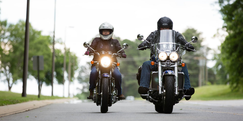Two motorcyclists driving down the street