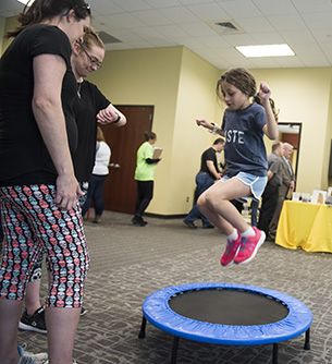 Child jumping on a trampoline at STEM Open House