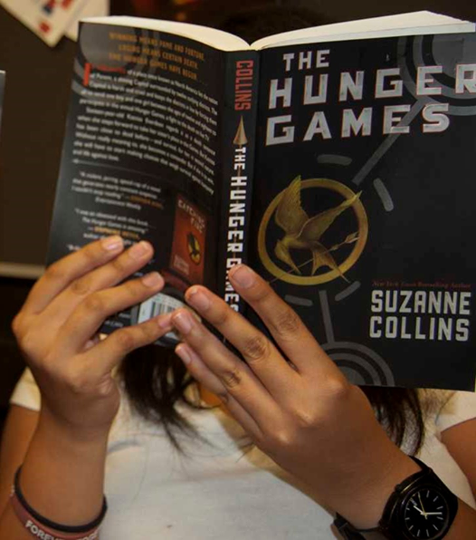 Girl reading the Hunger Games book