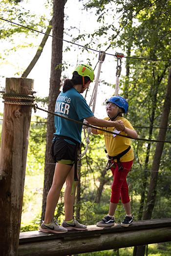 OTA student helping child walk across rope bridge